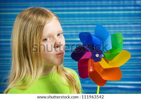 Children with rainbow pinwheel on a striped blue background - stock photo