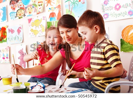 Children  with teacher draw paints in play room. Child care. - stock photo