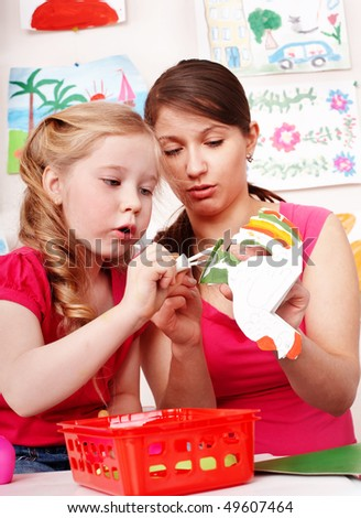 Children with teacher in play room. Preschooler. - stock photo