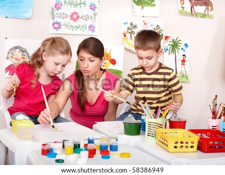 Children with teacher painting in play room. Preschool. - stock photo