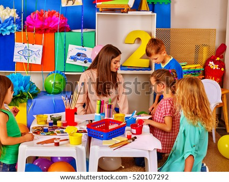 Children with teacher woman painting on paper at table in kindergarten . Children with teacher make overall project.