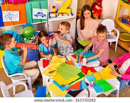 Children with teacher woman painting on paper in  kindergarten .  - stock photo