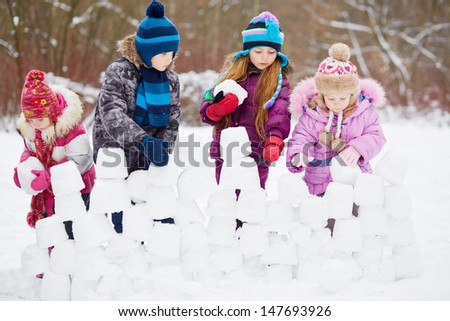 Children work at building wall from snow blocks in winter park - stock photo