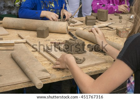 Children working with clay on a table - stock photo