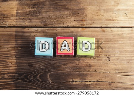 Childrens cubes with dad sign on wooden background - stock photo