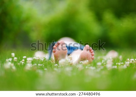 Childrens feet on grass outdoors in summer park - stock photo