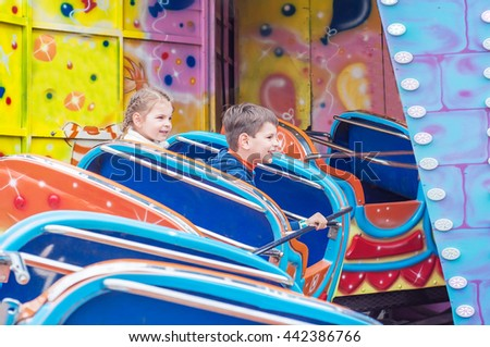 Childrens  in amusement park. Kids having fun. Funny kids and happy childhood.