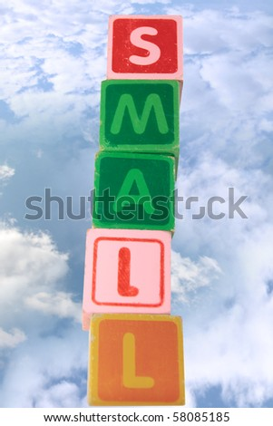 childrens toy letter building blocks against a cloudy background spelling small with clipping path - stock photo