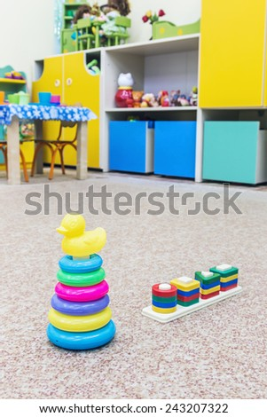 childrens toys scattered on the floor in a kindergarten - stock photo