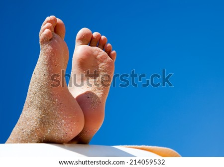 Childs feet relaxing and sunbathing on the beach concept for vacation and summer holiday - stock photo