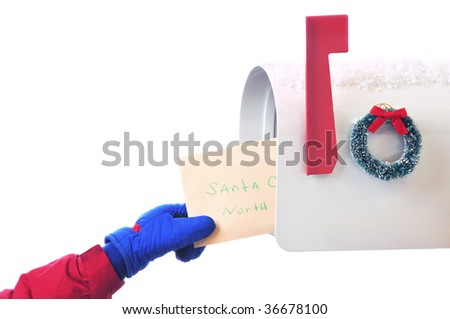 Childs hand placing letter to Santa Claus in Mailbox isolated on white. Horizontal Composition - stock photo