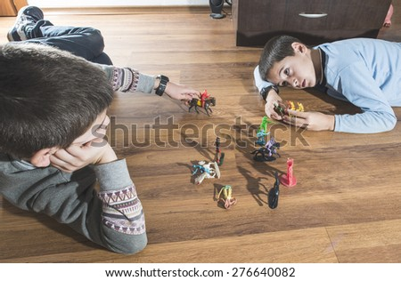 Childs playing with small vintage toys on the floor - stock photo