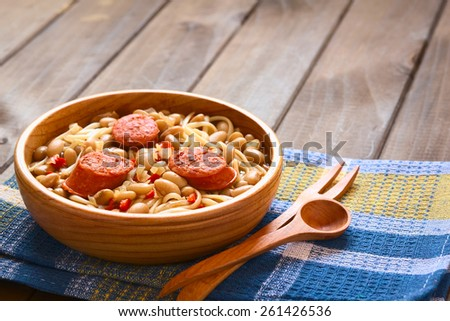 Chilean dish Porotos con Riendas (in English beans with reins) made of beans, linguine (flat spaghetti), fried sausage, photographed with natural light (Selective Focus, Focus one third into the dish) - stock photo