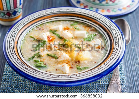 Chilean quinoa soup with cheese and milk. Spicy soup with quinoa, feta, coriander and milk - stock photo