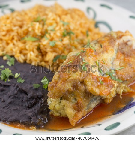 Chiles rellenos stuffed with a mixture of spiced ground pork and chicken, served with rice and beans - stock photo