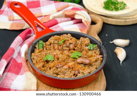 chili con carne in a cast iron skillet on a wooden board horizontal - stock photo