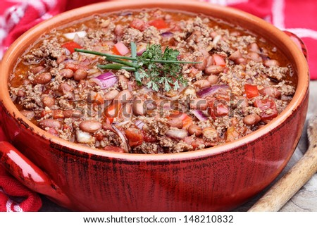 Chili Con Carne in a red ceramic pot.  - stock photo