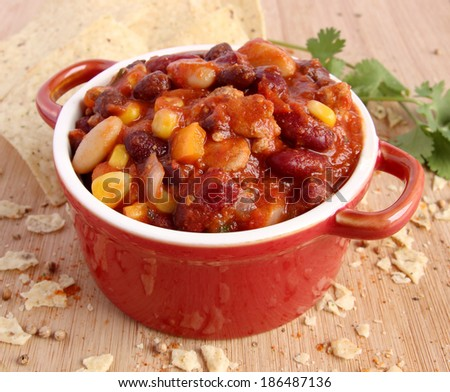 Chili con carne in red bowl with nacho chips and spice on wooden board