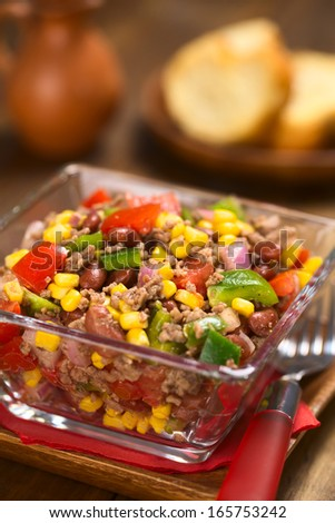 Chili con carne salad made of mincemeat, kidney beans, green bell pepper, tomato, sweet corn and red onions served in glass bowl (Selective Focus, Focus one third into the salad) - stock photo