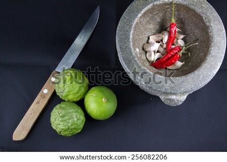 Chili, garlic in stone mortar  and  lemon,kaffir,kinfe Thai food ingredients - stock photo