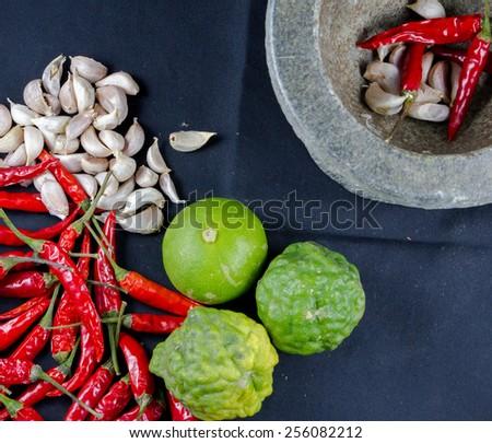 Chili, garlic in stone mortar  and  lemon,kaffir Thai food ingredients - stock photo