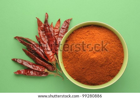 chili powder in green bowl on green background - stock photo