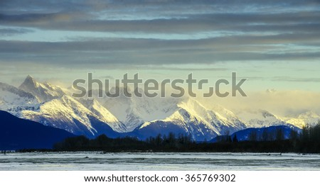 Chilkat River and Mountains in snow on a sunrise. Winter in Alaska.USA - stock photo