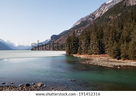 Chilkoot Lake near Haines Alaska in spring with ice melting and a bright blue sky.