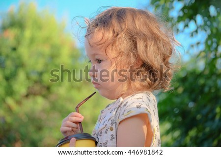 Chill out in the daytime. A toddler girl with blonde curly hair is drinking milk from a straw truing side in the public park. - stock photo
