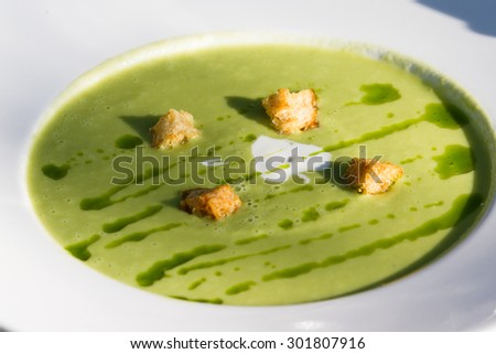chilled asparagus soup served with a cream and oil garnish and croutons - stock photo