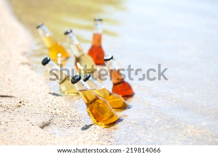 Chilled bottle of beer on beach - stock photo