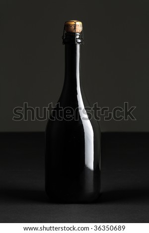 Chilled bottle of champagne on dark background - stock photo