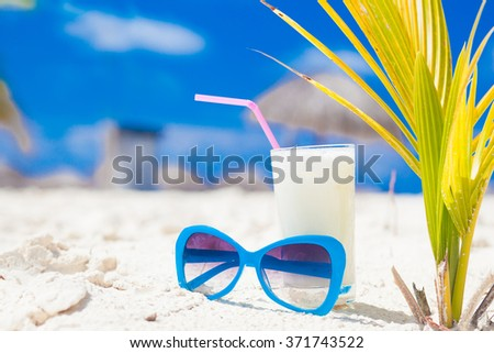 chilled cocktail pina colada and sunglasses on a sand beach - stock photo
