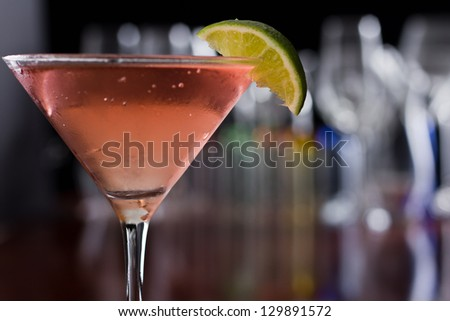 chilled cosmopolitan cocktail served in a  martini glass on a busy bar with a shallow depth of field with blurred glasses and lights in the back, garnished with a lime - stock photo