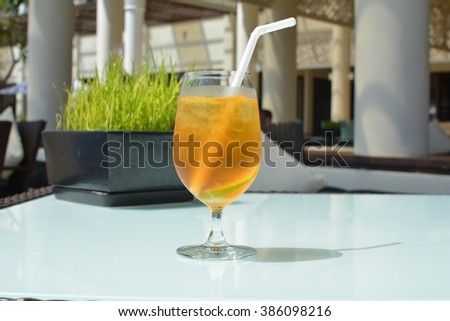 Chilled Fresh Ice Tea Drink  Set on a White Glass Table with a Black Pot of Green Rice Plant Growing and a  Venue Interior in the Background - stock photo