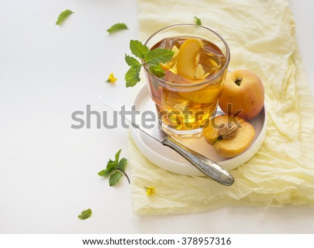 Chilled peach tea in glass with fresh cut peaches on white background. Text space image. - stock photo