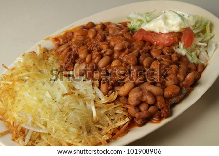 chilli beans / plate of chilli beans served with hash brown and lettuce.