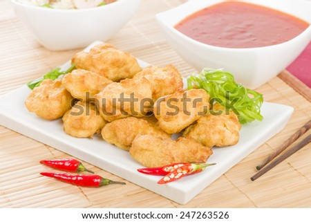 Chilli Chicken - Asian style battered and deep fried chicken pieces served with chilli sauce and special fried rice. - stock photo