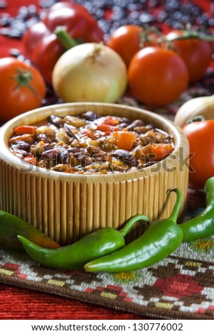 Chilli con carne in wooden bowl and different vegetables - stock photo