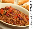 Chilli con carne served with a crusty bread baguette. - stock photo