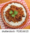 Chilli con carne with rice in terracotta dish - stock photo