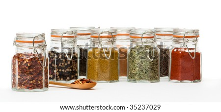 Chilli flakes on wooden spoon with row of spice jars - stock photo