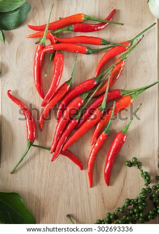chilli pepper on wooden board - stock photo
