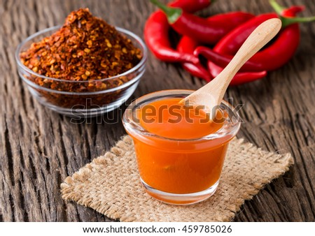 chilli sauce with red chilli and chilli powder on wooden background - stock photo