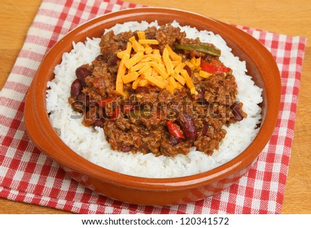 Chilli with rice and cheese in a terracotta dish - stock photo