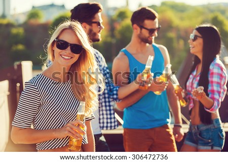 Chilling out with friends. Smiling young woman holding bottle of beer and looking at camera while three people talking to each other in the background - stock photo