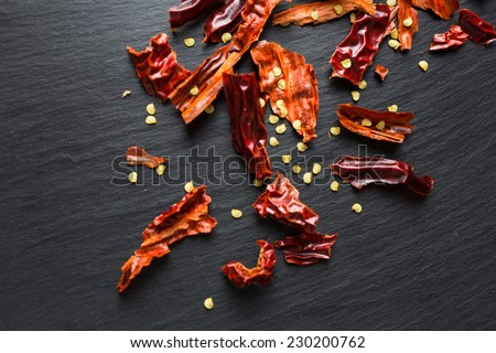 Chilly / chili flakes on black slate, top view - stock photo