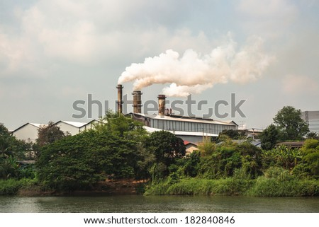 Chimney and white smoke in factory area - stock photo