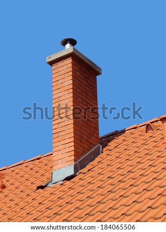 chimney in bright tile roof  with brick sunlight, against a blue sky