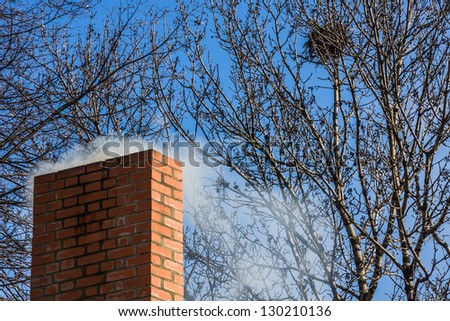 Chimney of brick against the blue sky. - stock photo